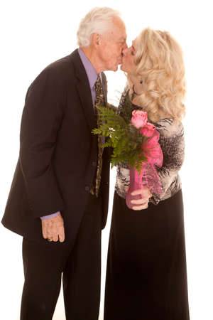 an elderly couple kissing, he gave her flowers. Imagens