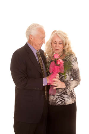 An older man is giving his wife flowers