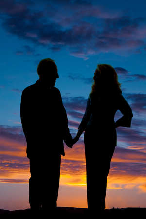 A silhouette of an older couple holding hands in the outdoors. Imagens