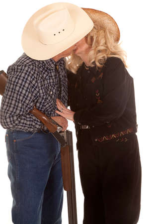 gun room: An elderly couple kissing while her cowboy is holding on to a shot gun. Stock Photo