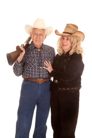 gun room: an elderly couple smiling while her cowboy is holding a shot gun over his shoulder.
