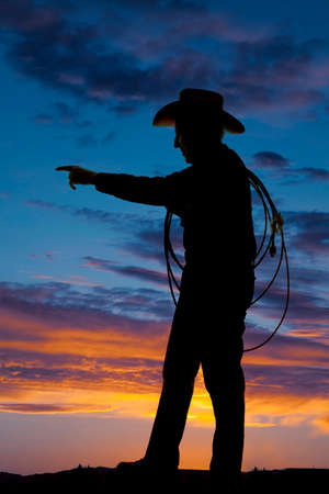 A silhouette of a older cowboy holding on to his rope. photo