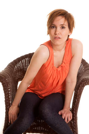A woman in an orange tank top sitting in a chair. photo
