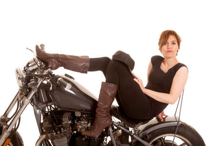 sexy boots: A woman is sitting on a motorcycle looking sexy.