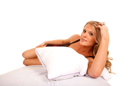 A woman is laying on her side in a bed behind a pillow. photo