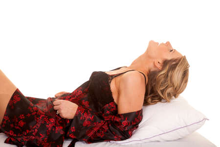 A woman in a black and red nightgown laying her head back on a pillow. photo