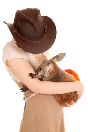 A woman holding a baby kangaroo in her arms. photo