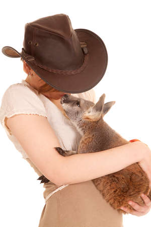 A latin woman is holding a baby kangaroo in her arms. photo