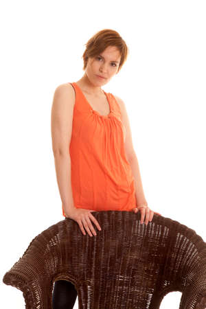 A Latin woman in an orange tank top standing behind a chair. photo