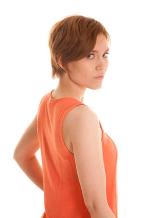 A woman in an orange tank top standing looking side. photo
