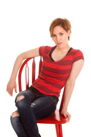 A woman in a red chair is sitting and looking. photo