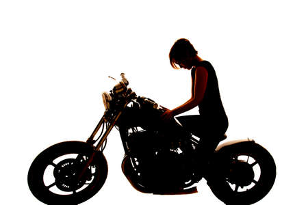 A woman is sitting on a motorcycle looking down silhouette. photo