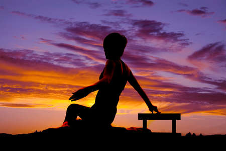A woman is sitting as a silhouette in the sunset. photo