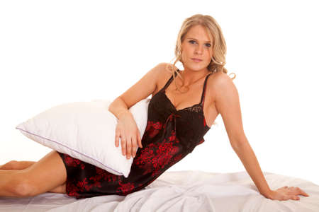 A woman in a black and red nightgown sitting on a bed looking. photo