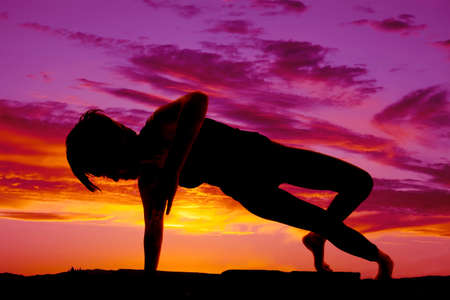 A silhouette of a woman dancing in the sunset. photo
