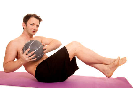A man is doing a crunch holding a medicine ball. photo