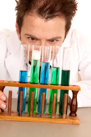 A man is looking at chemicals in several different test tubes. photo