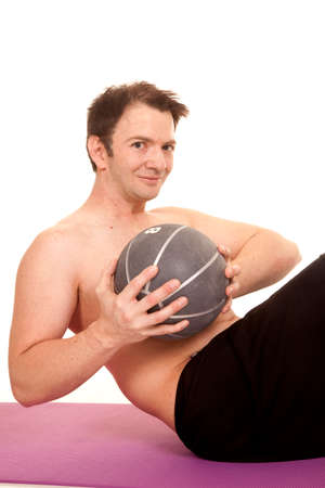 A man is holding a medicine ball working his abs. photo