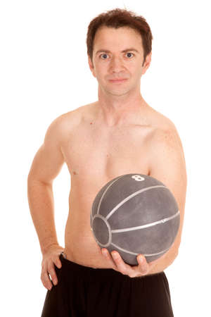 A man with no shirt on holding out a medicine ball