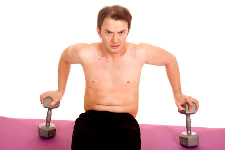 A man is sitting on weights working out. photo