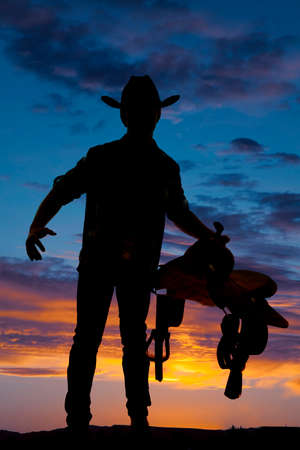 A silhouette of a cowboy holding a saddle in the sunset. photo