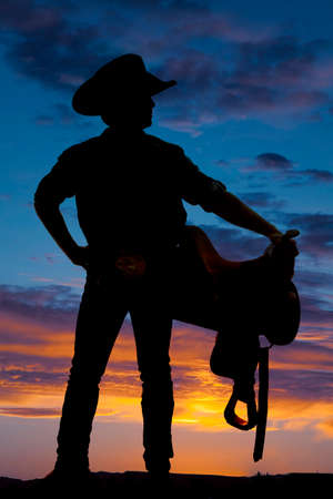A cowboy is holding a saddle on his hip in the sunset.