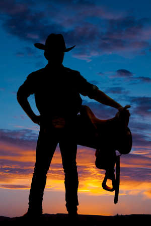 A silhouette of a man cowboy holding a saddle. photo