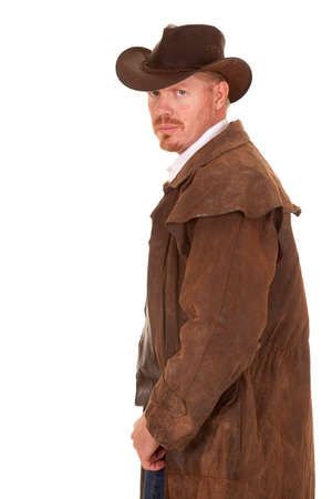 A cowboy in a leather coat looking back over his shoulder. photo