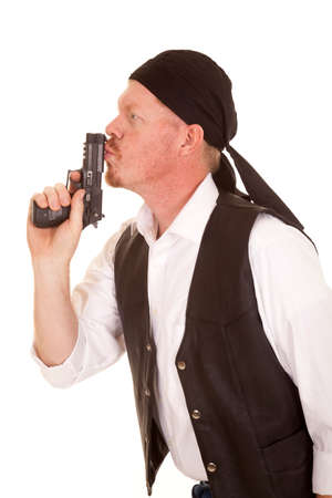 A man in a bandana and black vest is kissing a gun. Stock Photo
