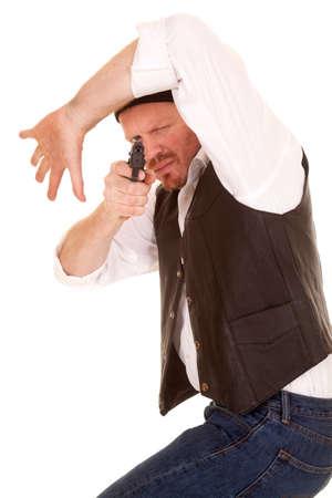 A man looking under his arm aiming a gun. photo
