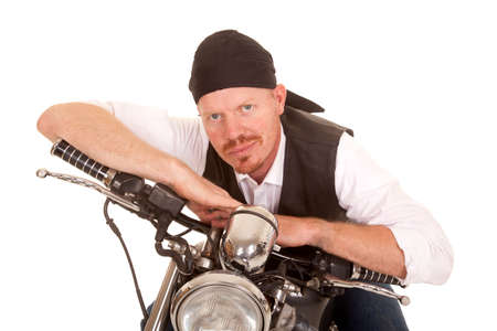 A man on a motorcycle leaningon the handlebars happy. photo