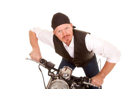 leaning forward: A man standing on a motorcycle leaning forward.