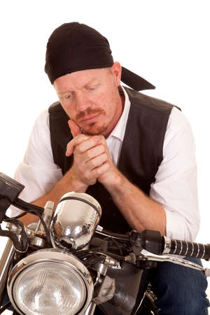 A man on a motorcycle with his hands together looking down. photo