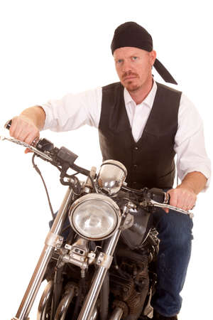 A man on a motorcycle sitting with a serious expression on his face. photo
