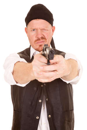 A man in a vest aiming a gun with one eye closed. photo