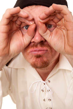 A man is looking through his fingers with wide eyes. photo