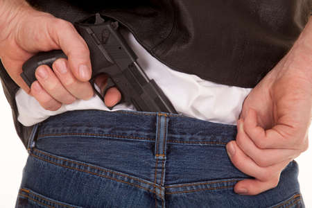 concealed: A man is pulling a gun out of the back of his pants. Stock Photo