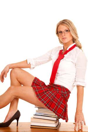 falda corta: Una niña de la escuela se encuentra en una pila de libros que parece seria.
