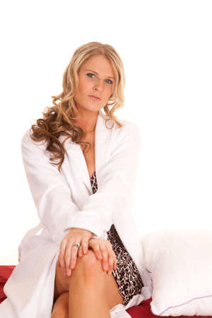 one sheet: A woman in a white robe sitting on a bed. Stock Photo