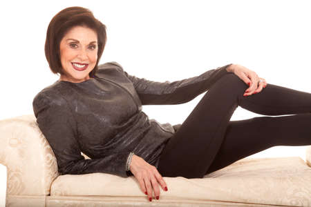 An older woman in her black leggings and gray jacket laying on a couch.