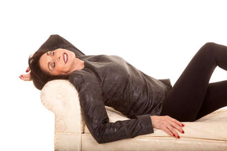 an older woman laying back on her couch. Stock Photo