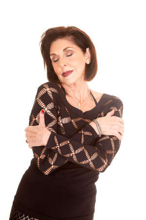 an older woman in her black top hugging herself with her eyes closed.