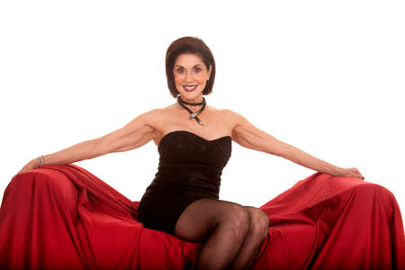 An older woman in her short black dress sitting on a red couch. photo
