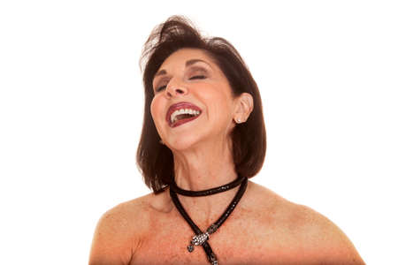 An older woman laughing with her head tilted back, bare shoulders. photo