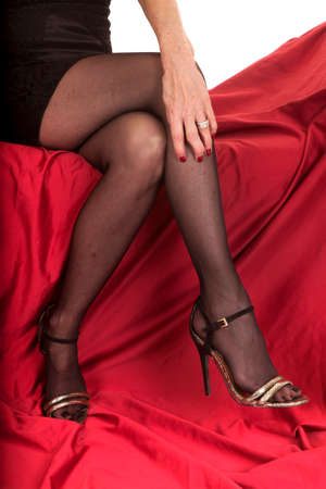 An older woman in her heels and stockings sitting on a red couch. photo