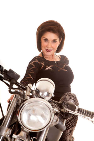 an older woman sitting on a motorcycle posing. photo
