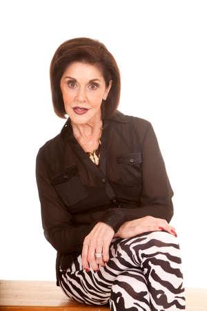 An older woman sitting on a bench in her zebra leggings.