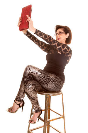 An older woman sitting on a stool using her tablet Stock Photo
