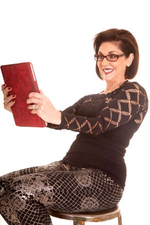 An older woman sitting on a stool holding on to her tablet.