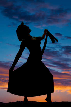 a silhouette of a woman playing with her dress. photo